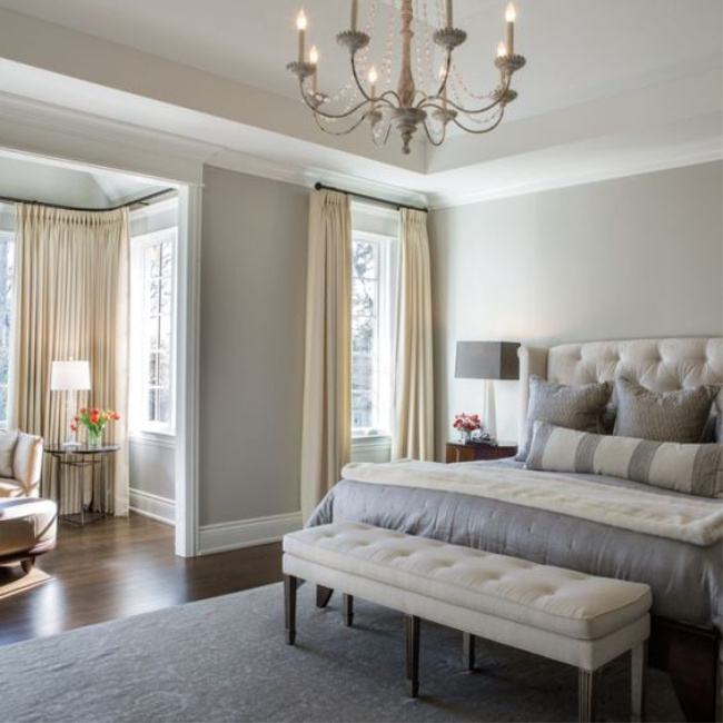 Benjamin Moore Revere Pewter in a luxurious French country bedroom with tufted headboard and bench. #paintcolors #reverepewter #benjaminmoore #bedroom #bestwhitepaint