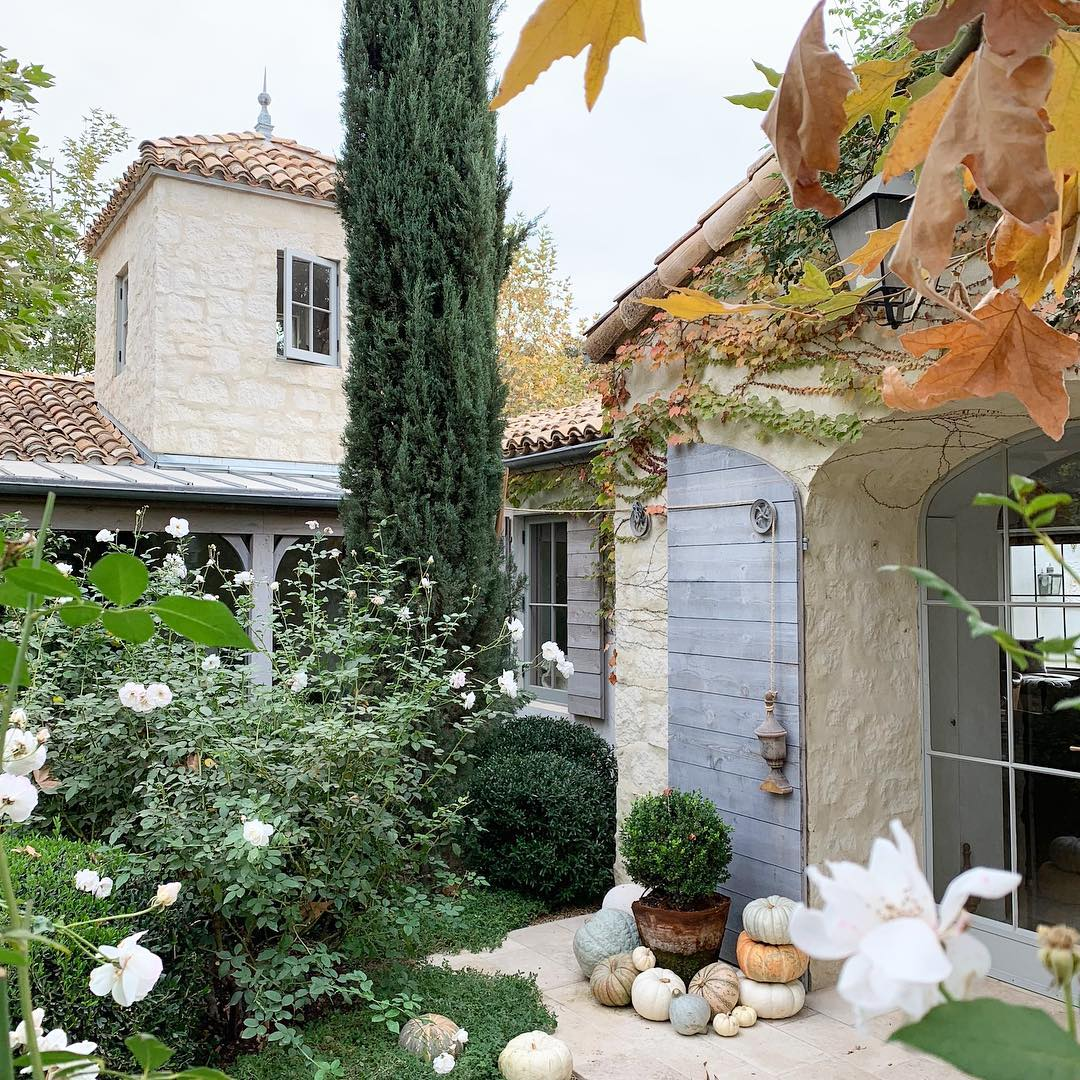 Patina Farm exterior in fall with rustic shutters, rugged stone, and lush gardens. Brooke Giannetti. #patinafarm #exterior #stonefarmhouse #modernfarmhouse #frenchfarmhouse #fallgarden #ojaicalifornia #giannettihome