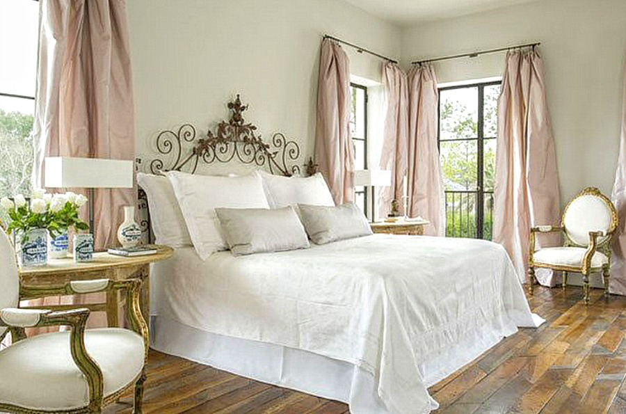 Elegant bedroom with French inspired decor, blush taffeta curtains, white bedding, and rustic wood floors. Come enjoy photos of this house tour with architecture by Reagan Andre.