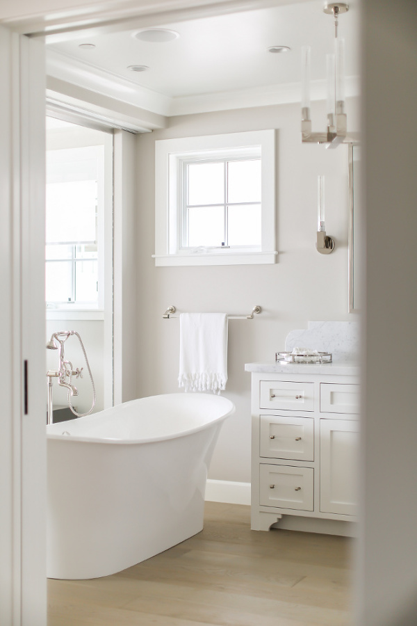 Collonade Gray by Sherwin Williams is the paint color on walls of this glorious and serene bathroom by Melissa Morgan Design. #paintcolors #collonadegray #sherwinwilliams #paintcolors