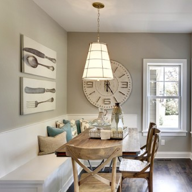 Collonade Gray paint color by Sherwin Williams on the walls of a darling breakfast nook with built-in banquette and oversized clock and art. #collonadegray #sherwinwilliams #paintcolors #lightgrey #bestneutralpaint