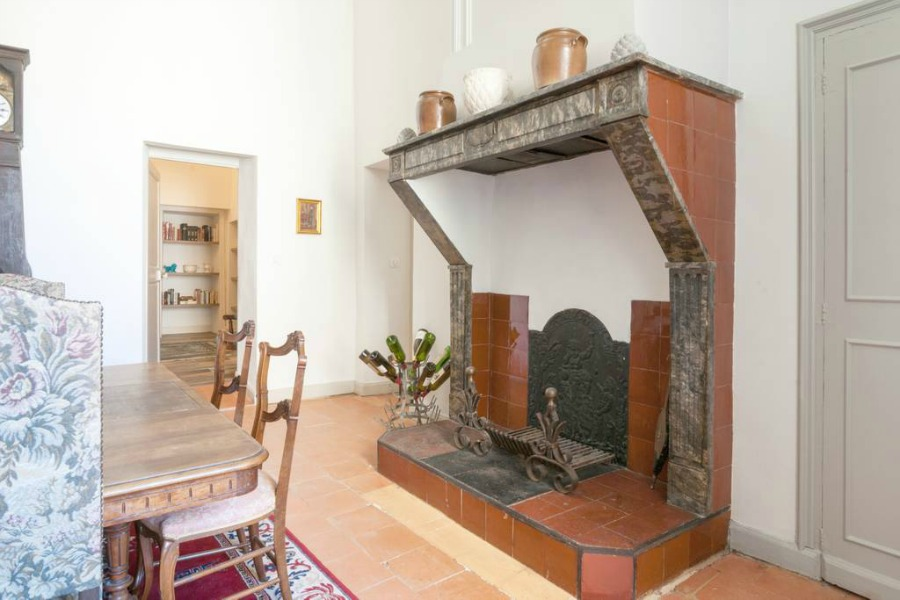 Kitchen fireplace. Classic French apartment with luxurious interiors has been fully renovated to high standards in Carcassonne, France and is available to rent - L'ancienne Tannerie.