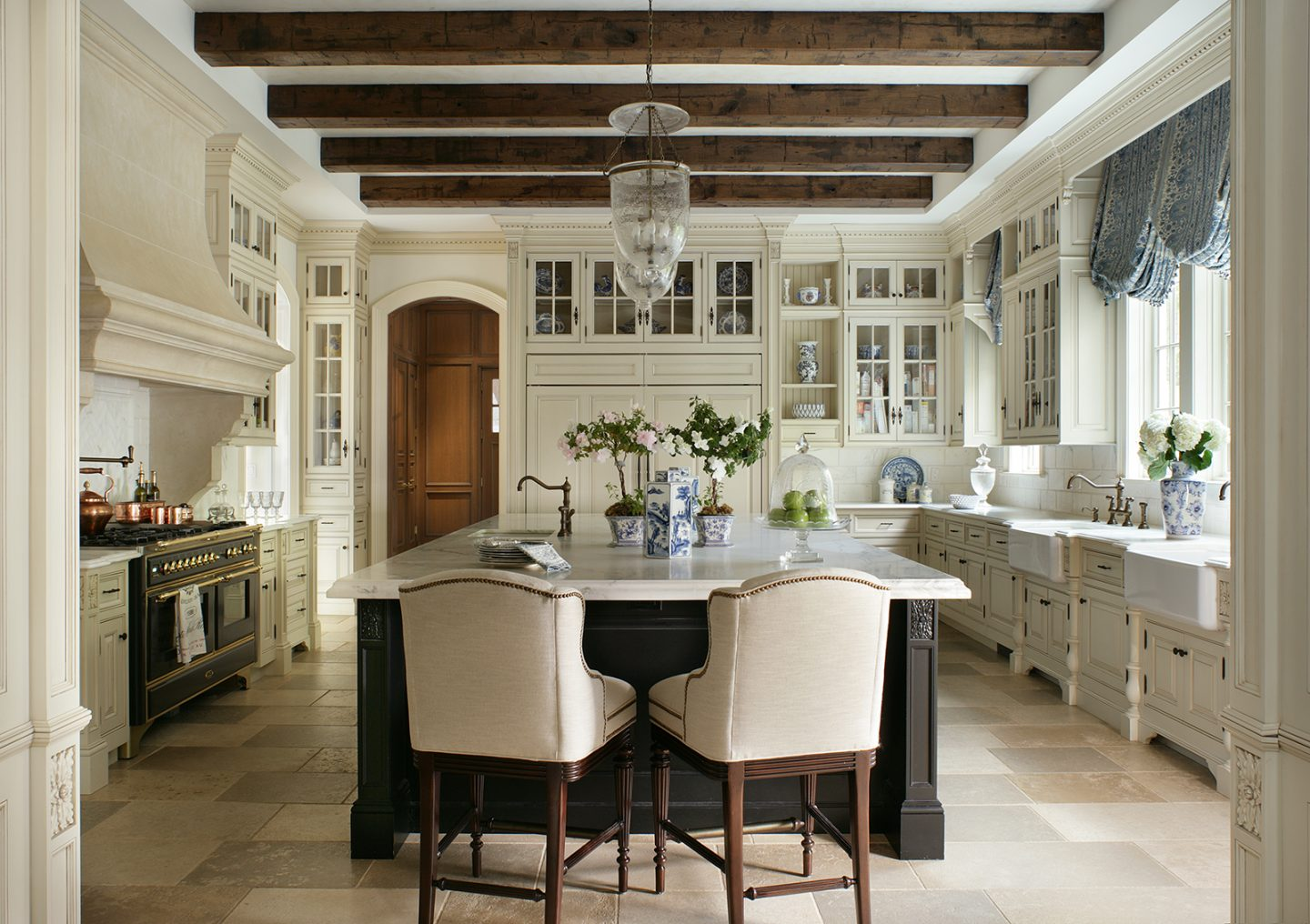 Luxurious blue and white French country kitchen with wood beams, two farm sinks, and island. The Enchanted Home.
