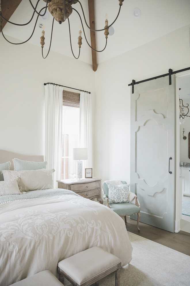 French country farmhouse bedroom with Duck Blue barn door and Sherwin Williams Alabaster paint color on walls. Brit Jones Design.