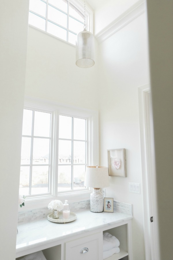 Elegant French country white bathroom with Sherwin Williams Alabaster paint on walls. Brit Jones Design.