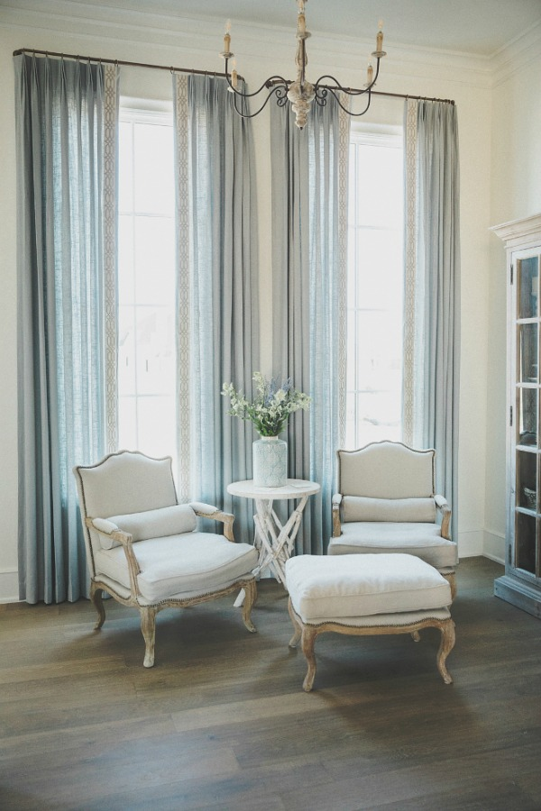 Classic French Bergere arm chairs and pale blue drapes in a French country room by Brit Jones with Sherwin Williams Alabaster paint.