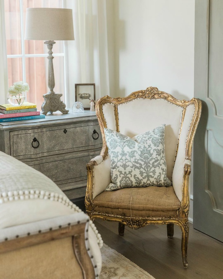 Wingback French chair French country farmhouse white bedroom. Sherwin Williams Alabaster paint color on walls. Brit Jones Design. See 18 Inspiring Country French Bedroom Decor Ideas!