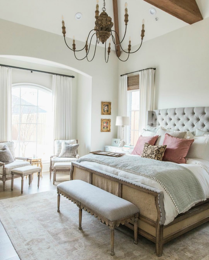 French country farmhouse white bedroom with tufted headboard and arch window bay. Sherwin Williams Alabaster paint color on walls. Brit Jones Design. See 18 Inspiring Country French Bedroom Decor Ideas!