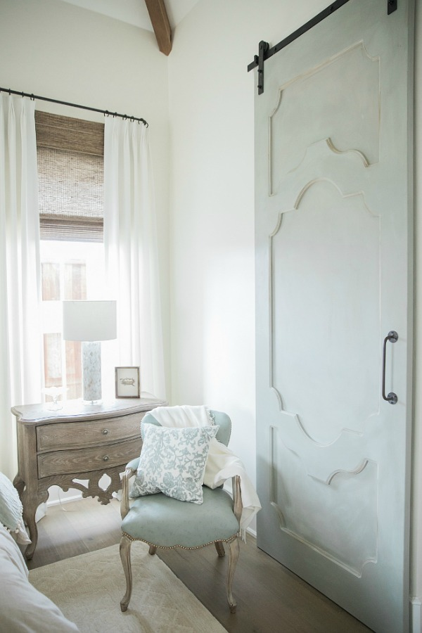 French country farmhouse white bedroom with Duck Egg blue barn door. Sherwin Williams Alabaster paint color on walls. Brit Jones Design. See 18 Inspiring Country French Bedroom Decor Ideas!