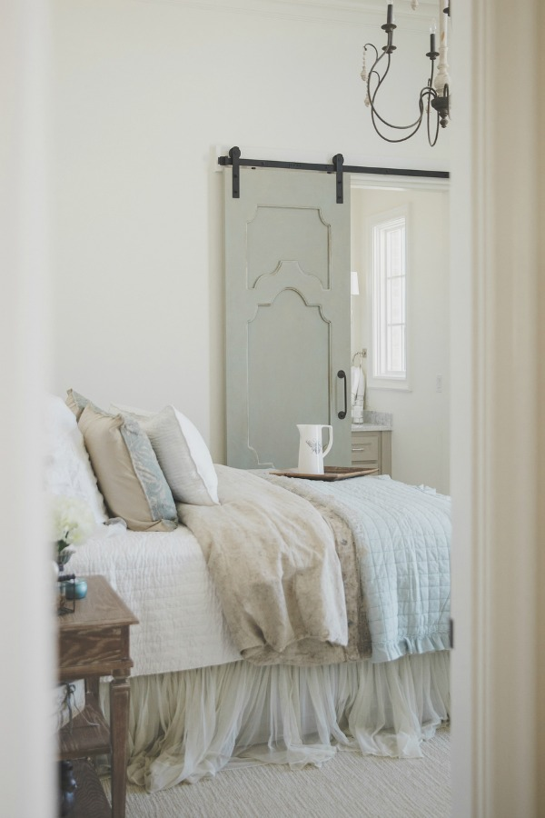 French country farmhouse pale blue and white bedroom with Duck Egg blue barn door. Sherwin Williams Alabaster paint color on walls. Brit Jones Design. See 18 Inspiring Country French Bedroom Decor Ideas!