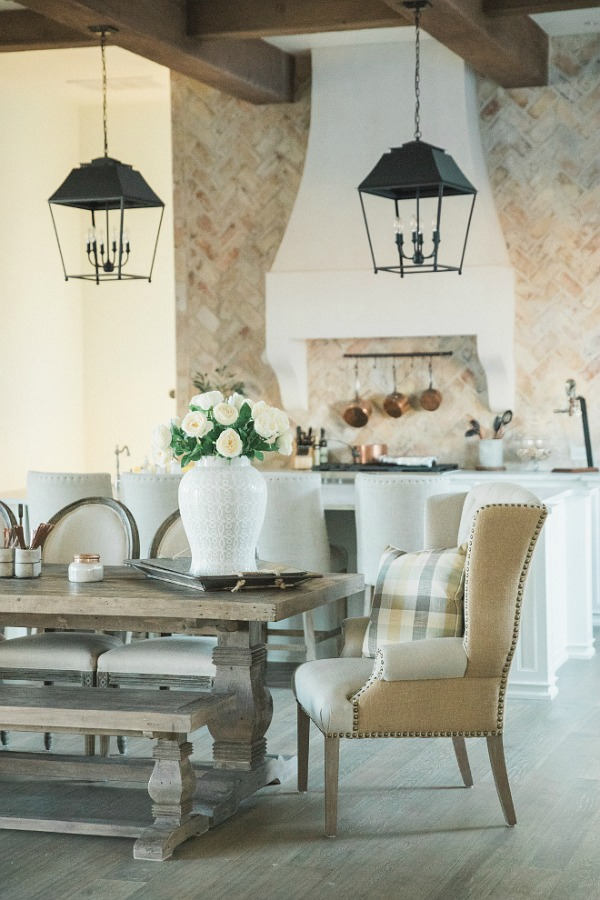 French country farmhouse kitchen with rustic lanterns, farm table, wing chairs, reclaimed Chicago brick, and Sherwin Williams Alabaster white paint on walls. Brit Jones Design.
