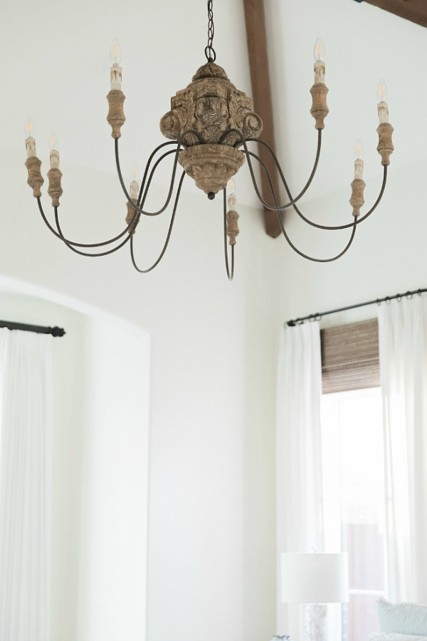 Detail of rustic French country chandelier in bedroom with Sherwin Williams Alabaster paint color. Brit Jones Design.