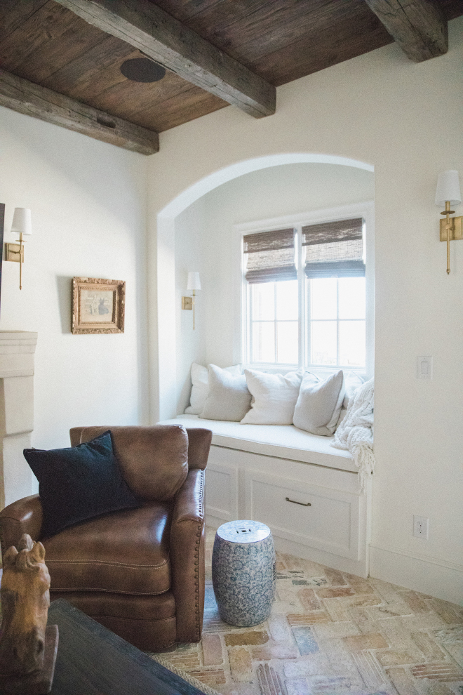 Charming French country den painted Sherwin Williams Alabaster with leather chair and arched detail over window seat nook. Brit Jones Design.