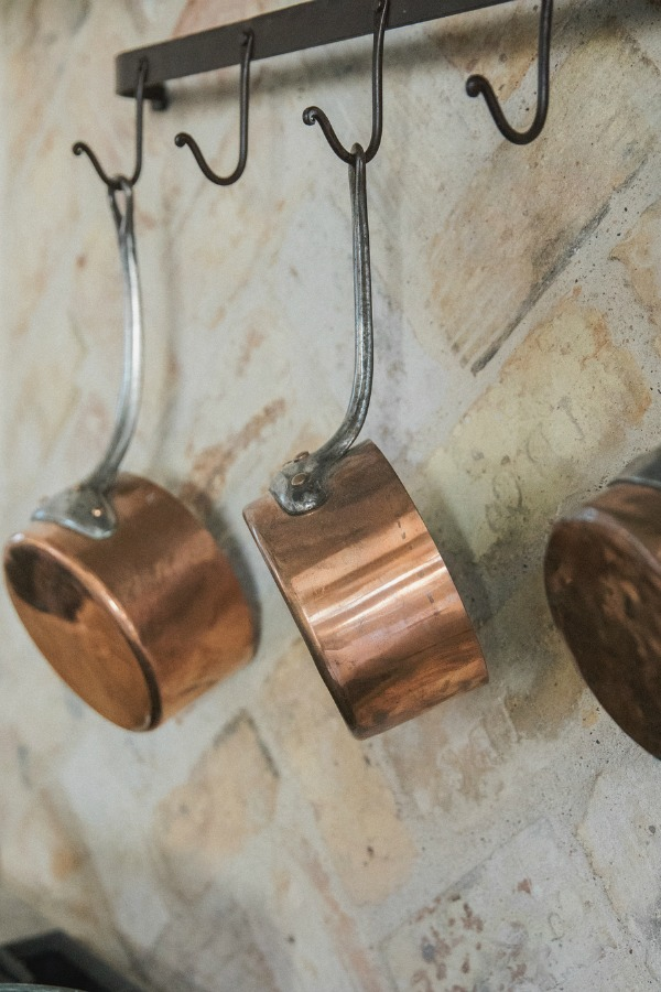 Detail of copper pots and reclaimed Chicago brick backsplash in French country kitchen by Brit Jones.