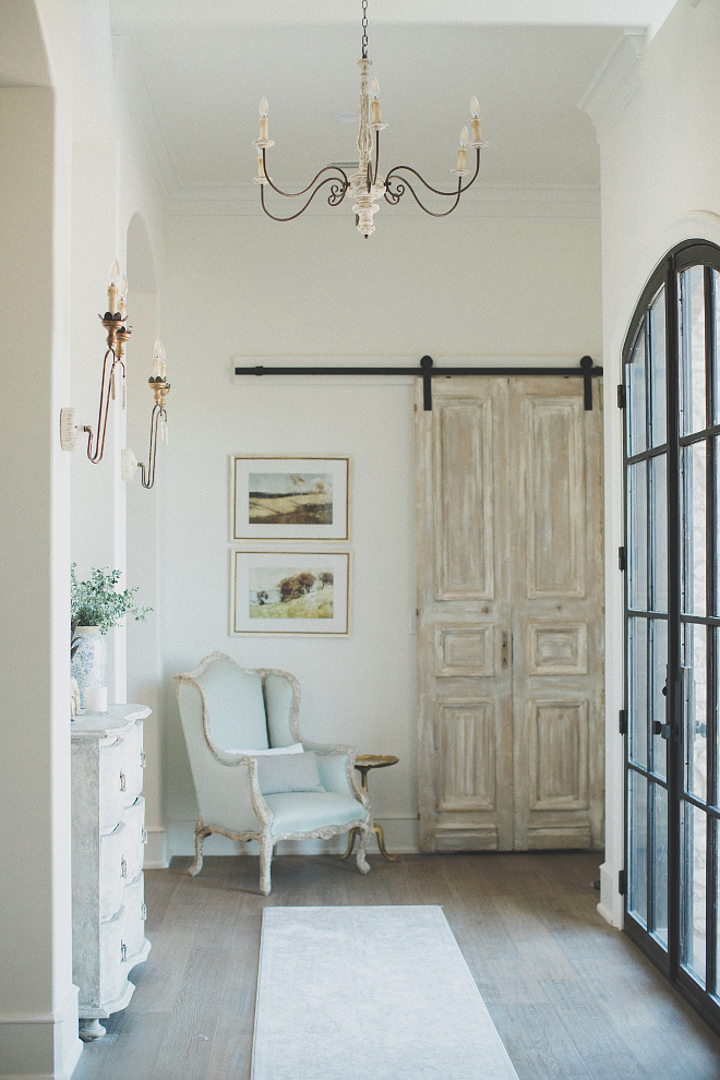 French country farmhouse entry with rustic barn door, wingback chair, steel windows, chandelier and wall sconces. Brit Jones Design.