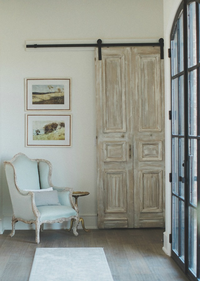 Sherwin Williams Alabaster paint color in a French country farmhouse entry with rustic barn door, wingback chair, steel windows, chandelier and wall sconces. Brit Jones Design. #sherwinwilliamsalabaster #paintcolors #warmwhite #whitepaintcolors #frenchcountry
