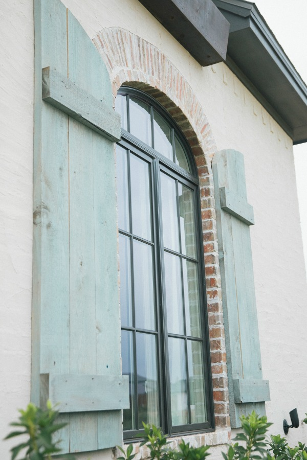 Detail of rustic blue shutters on arch window of French country home exterior. Brit Jones Photography.