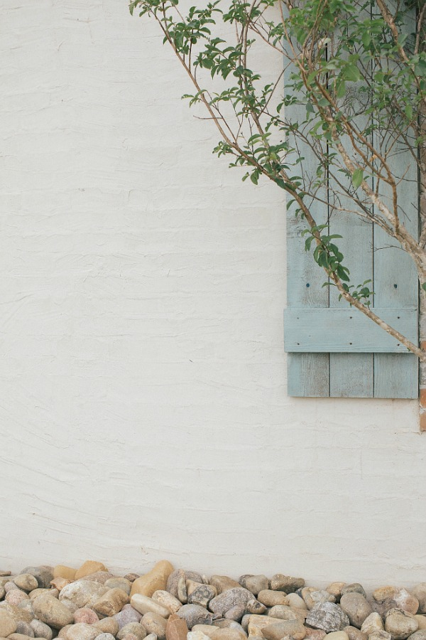 Detail of white exterior brick slurry with stucco over brick and rustic light blue shutters. Brit Jones Design.
