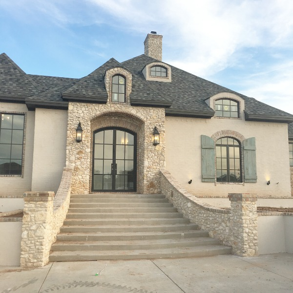 French country home exterior with arches, rustic shutters, brick, stone, and stucco. Brit Jones Design.