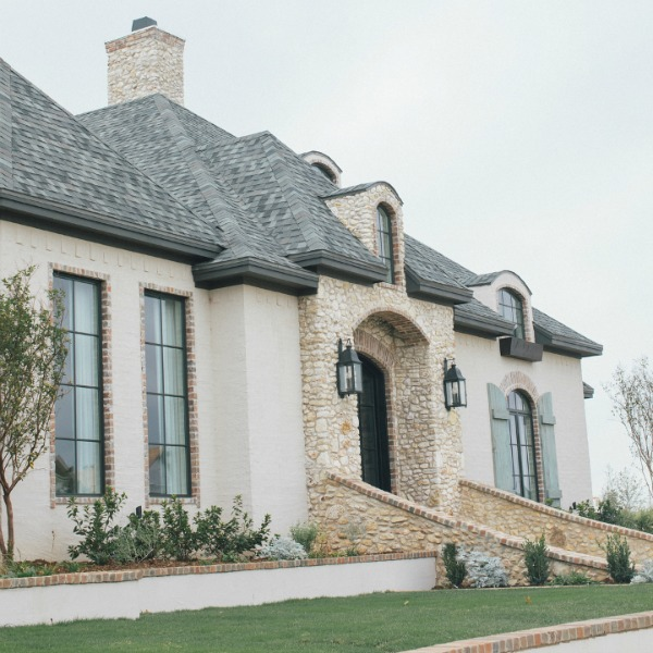 French country home exterior with brick, stone, rustic shutters and arches.