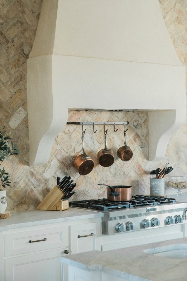 Rustic elegant French country farmhouse kitchen with beautiful stucco range hood, copper pots, reclaimed Chicago brick backsplash, arabescato marble counters, and lanterns over island. Brit Jones Design.  See more Gorgeous European Country Interior Design Inspiration on Hello Lovely. #europeancountry #frenchfarmhouse #interiordesign