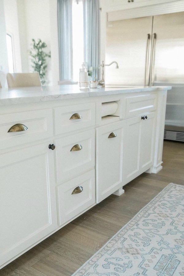 Detail of beautiful white Shaker style island topped with honed arabescato marble in French country kitchen with oak hardwood flooring. Brit Jones Design.