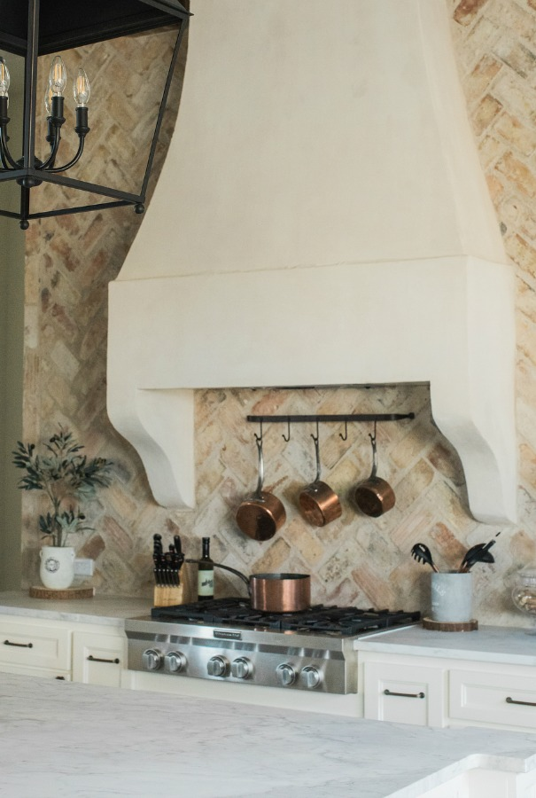 Rustic elegant French country farmhouse kitchen with beautiful stucco range hood, copper pots, reclaimed Chicago brick backsplash, arabescato marble counters, and lanterns over island. Brit Jones Design. Come see 24 Inspiring European Country Kitchen Ideas!