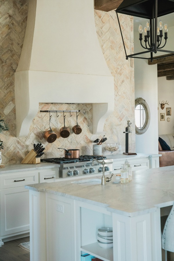 Rustic elegant French country farmhouse kitchen with beautiful stucco range hood, copper pots, reclaimed Chicago brick backsplash, arabescato marble counters, and lanterns over island. Brit Jones Design.