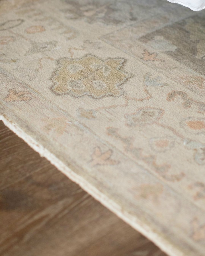 Detail of pale pastel pattern rug runner in French country farmhouse kitchen with wood floors. Brit Jones Design.