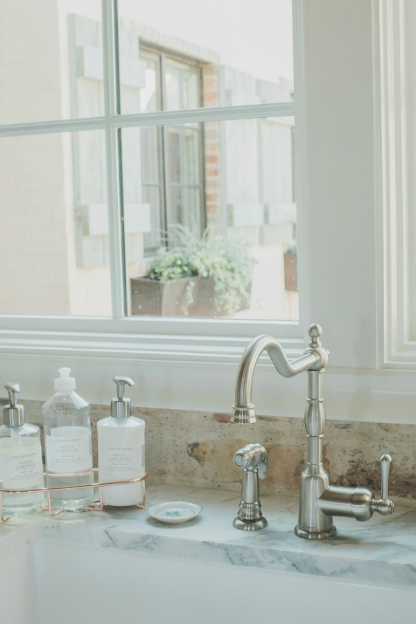 Detail of French style kitchen faucet and reclaimed Chicago brick backsplash and farm sink. Brit Jones Design.