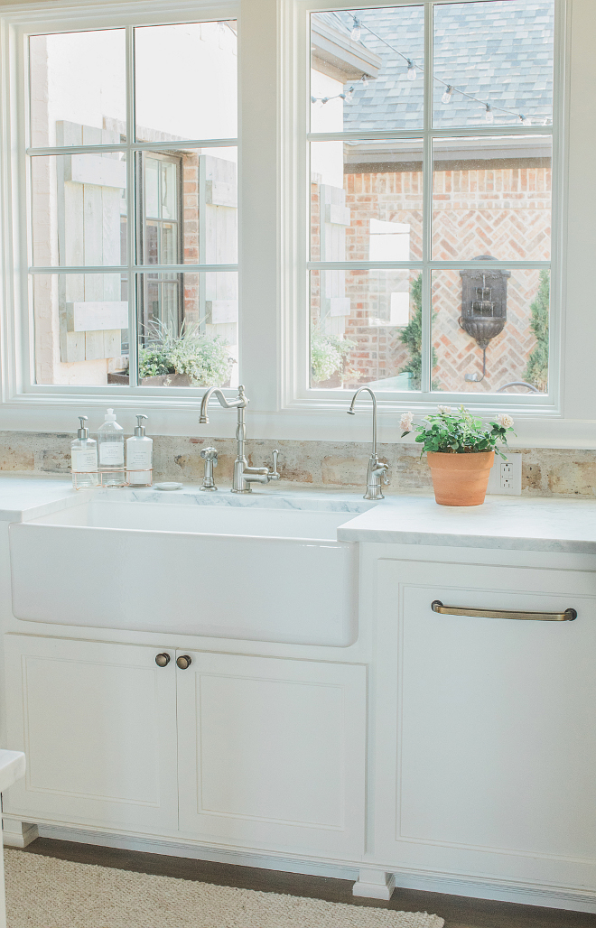 Rustic elegant French country farmhouse white kitchen with farm sink, reclaimed Chicago brick backsplash, and window overlooking courtyard. Brit Jones Design.