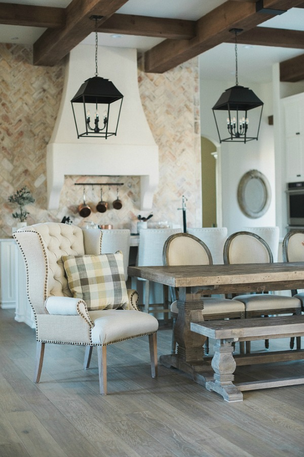 French country farmhouse kitchen with wingback chair, French dining chairs, farm table, rustic hanging lantern pendants, and reclaimed Chicago brick. Brit Jones Design.