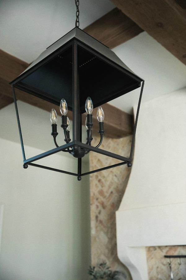 Detail of rustic French farmhouse hanging lantern pendant over island in French country kitchen by Brit Jones.