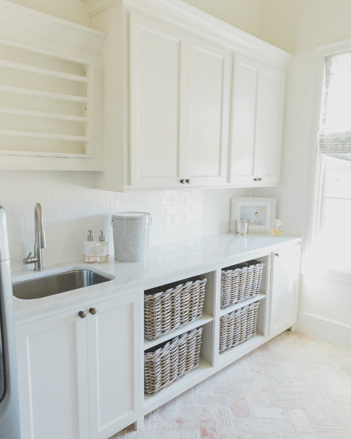 Sherwin Williams Alabaster paint color in rustic elegant French country laundry room. Open basket storage, reclaimed Chicago brick flooring, and abundant natural light. Brit Jones Design.