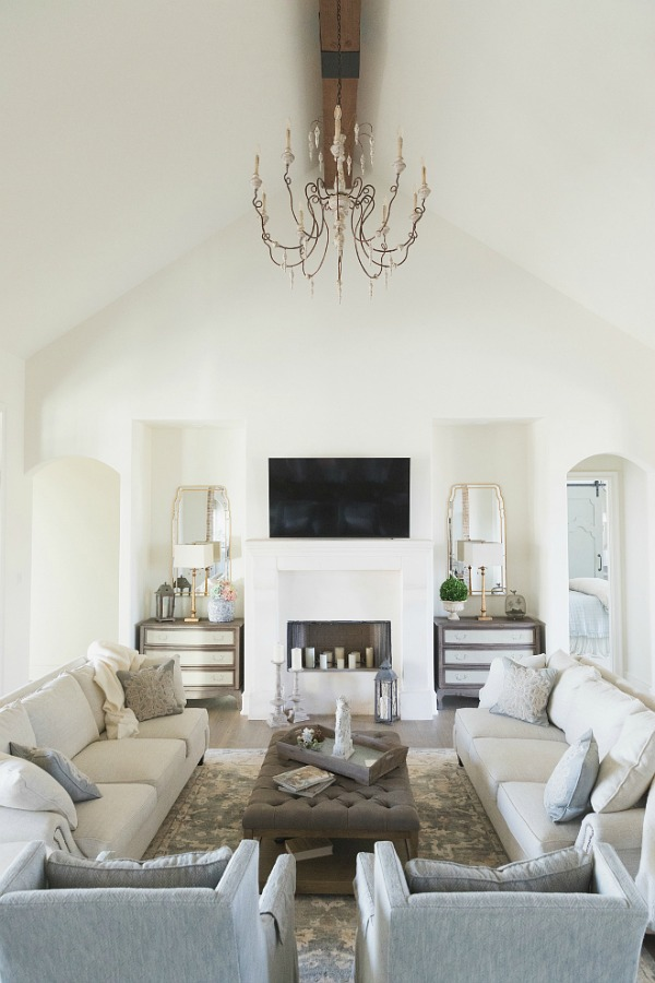 Sherwin Williams Alabaster paint color in elegant French country great room with cathedral ceiling, beams, fireplace, and French chandelier. Brit Jones Design.