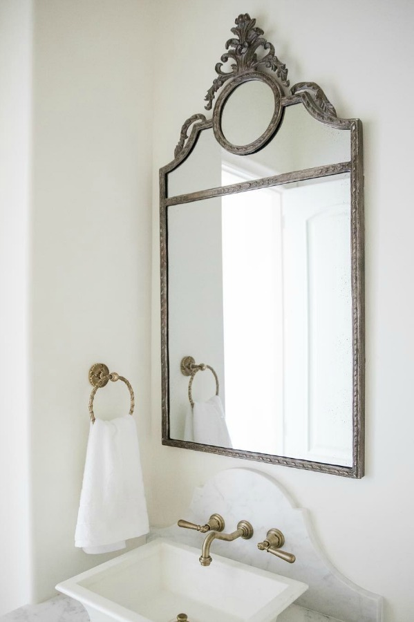 Sherwin Williams Alabaster paint color on walls of French country powder room with vessel sink and elegant mirror. Brit Jones Design.