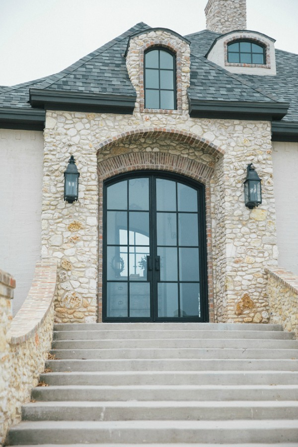 Elegant French country home esterior with steel double arch front doors, stone, brick, stucco, and rustic lanterns. Design by Brit Jones.