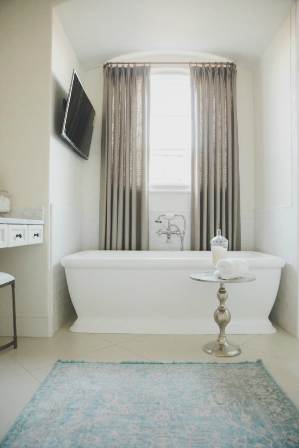 Serwin Williams Alabaster paint on walls. Elegant French country white bathroom with freestanding tub and drapes at window. Brit Jones Design.