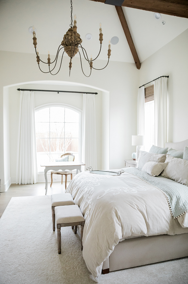 Airy, lofty, and elegant French country farmhouse bedroom with arches, desk, and bench. Brit Jones Design. See 18 Inspiring Country French Bedroom Decor Ideas!