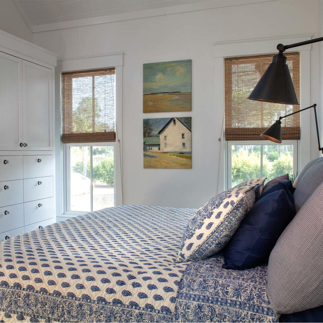 Coastal bedroom with blue paisley bedding, built-ins, and black swing arm task sconces - Lisa Furey. #coastalstyle #bedroomdesign #blueandwhite #coastalbedroom #interiordesign #cottagestyle