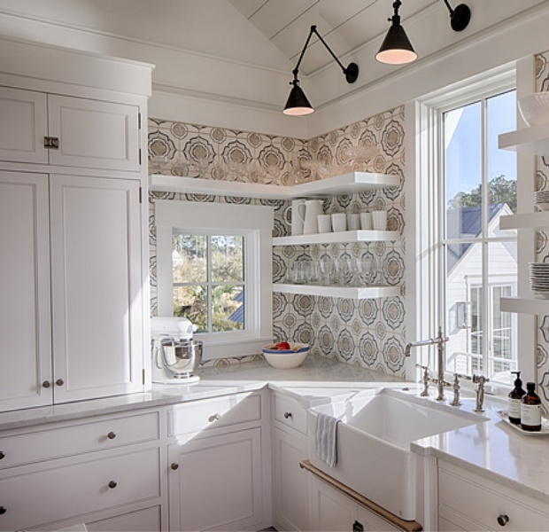 White coastal cottage kitchen with floating shelves, Shaker cabinets, white oak, and cement tile backsplash with blue accents. Lisa Furey. #coastalkitchen #whitekitchens #kitchendesign #modernfarmhouse #coastalcottage #cottagekitchen #floatingshelves #farmsink #shiplap