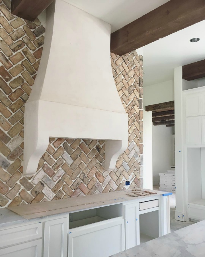 Under construction French country farmhouse kitchen with reclaimed Chicago brick ungrouted. Brit Jones Design.