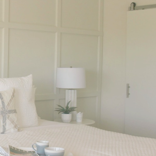Serene and sunny white bedroom in Arizona with board and batten panel wall and sliding modern barn door. Hello Lovely Studio.