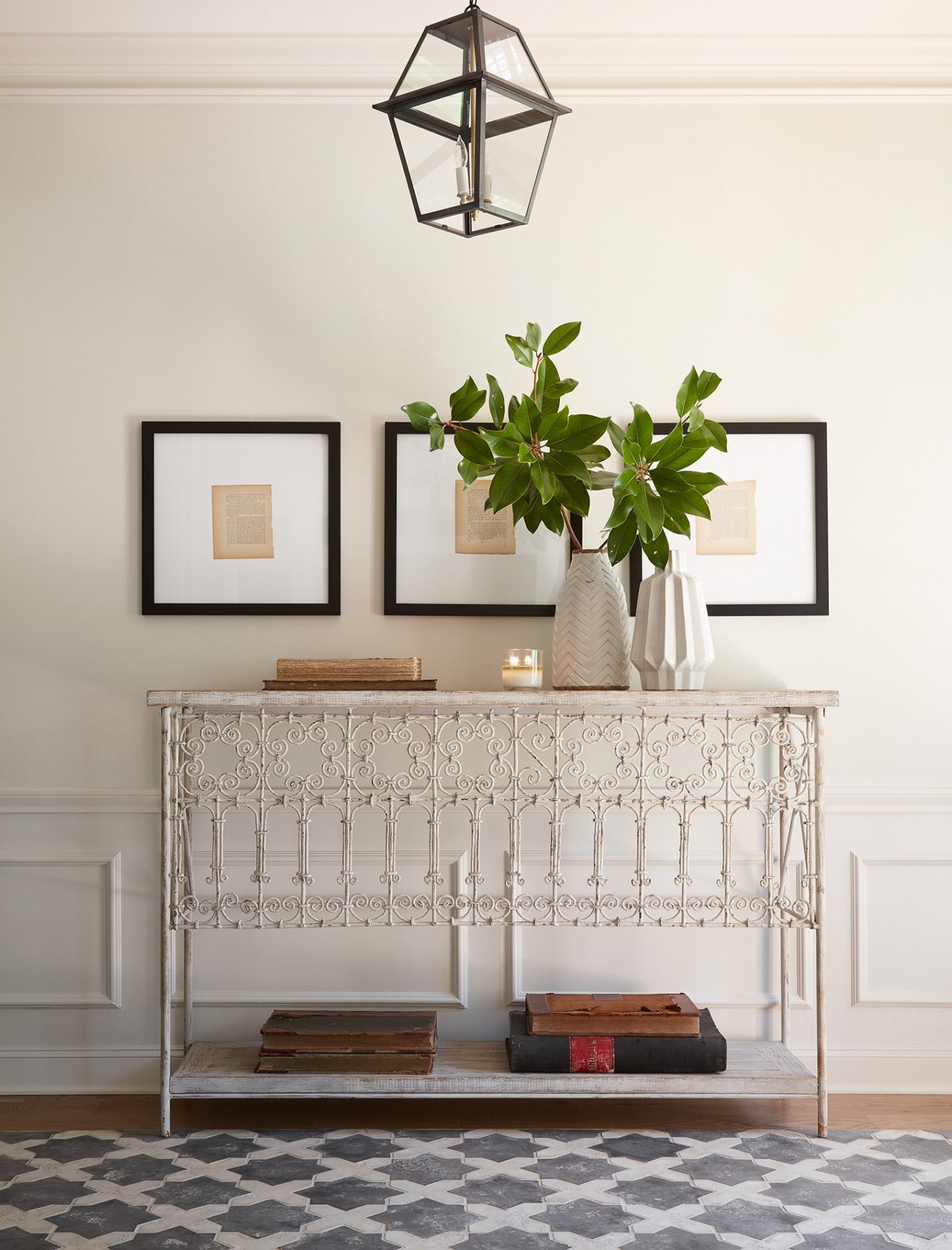 Gorgeous entryway in HGTV Fixer Upper's THE CLUB HOUSE episode! A vintage metal console table with delicate scrolling and encaustic tile rug in the white oak flooring. #fixerupper #theclubhouse #entryway #frenchfarmhouse #interiordesign #vintagestyle #consoletable