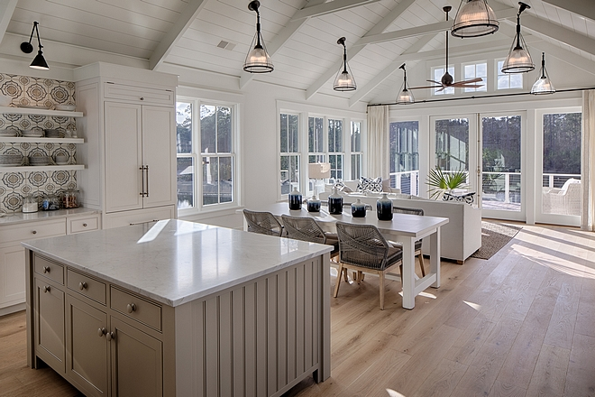 Classic white coastal cottage kitchen in Palmetto Bluff by Lisa Furey. Modern farmhouse design elements include floating shelves, shiplap, white oak flooring, and apron front farm sink.