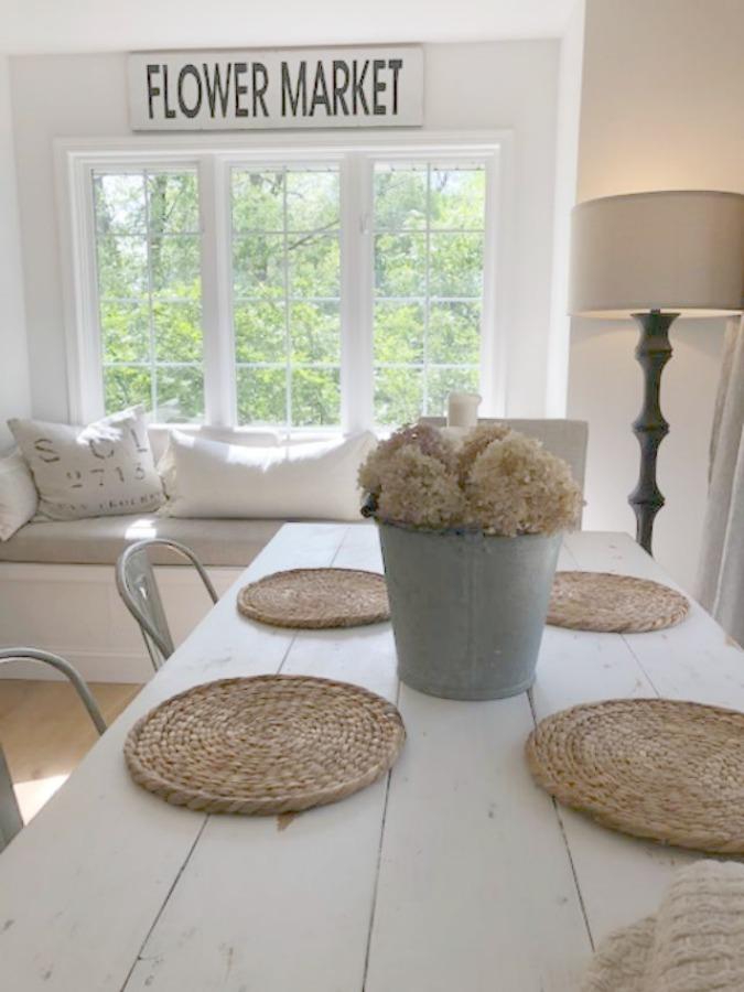 Serene tranquil white kitchen with farm sink, marble subway tile, Viatera Minuet quartz counters, white Shaker cabinets, and white oak flooring. Design and photo: Hello Lovely Studio. #kitchendesign #whitekitchen #minuet #whitequartz #benjaminmoorewhite