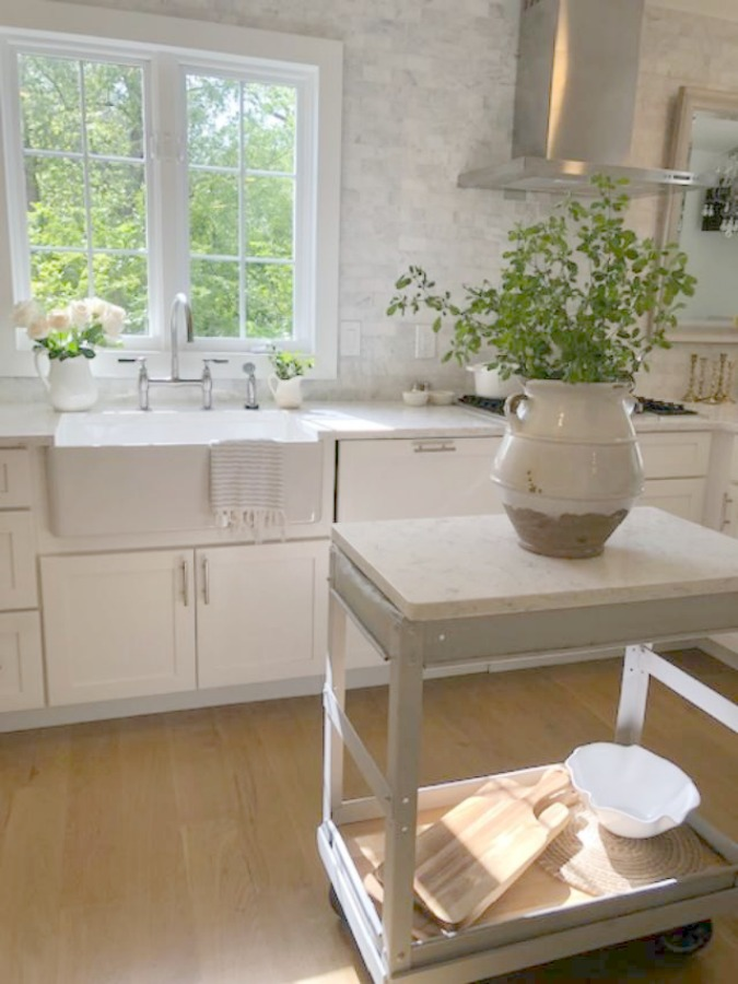 Serene tranquil white kitchen with farm sink, marble subway tile, Viatera Minuet quartz counters, white Shaker cabinets, and white oak flooring. Design and photo: Hello Lovely Studio. See more Gorgeous European Country Interior Design Inspiration on Hello Lovely. #europeancountry #frenchfarmhouse #interiordesign