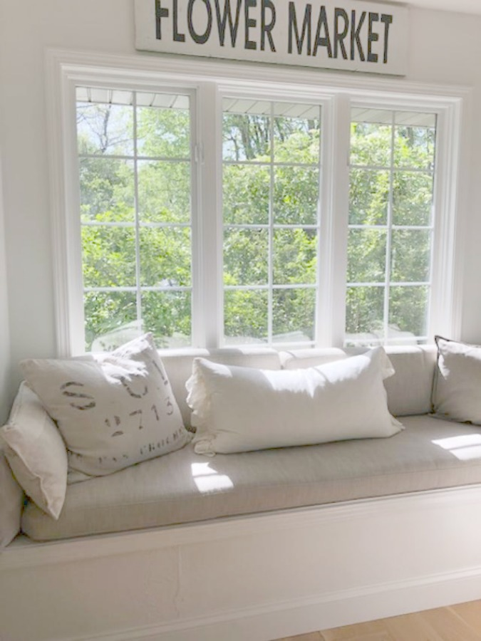 Window seat with linen pillows and cushions. Serene tranquil white kitchen. Design and photo: Hello Lovely Studio. #kitchendesign #whitekitchen #minuet #whitequartz #benjaminmoorewhite