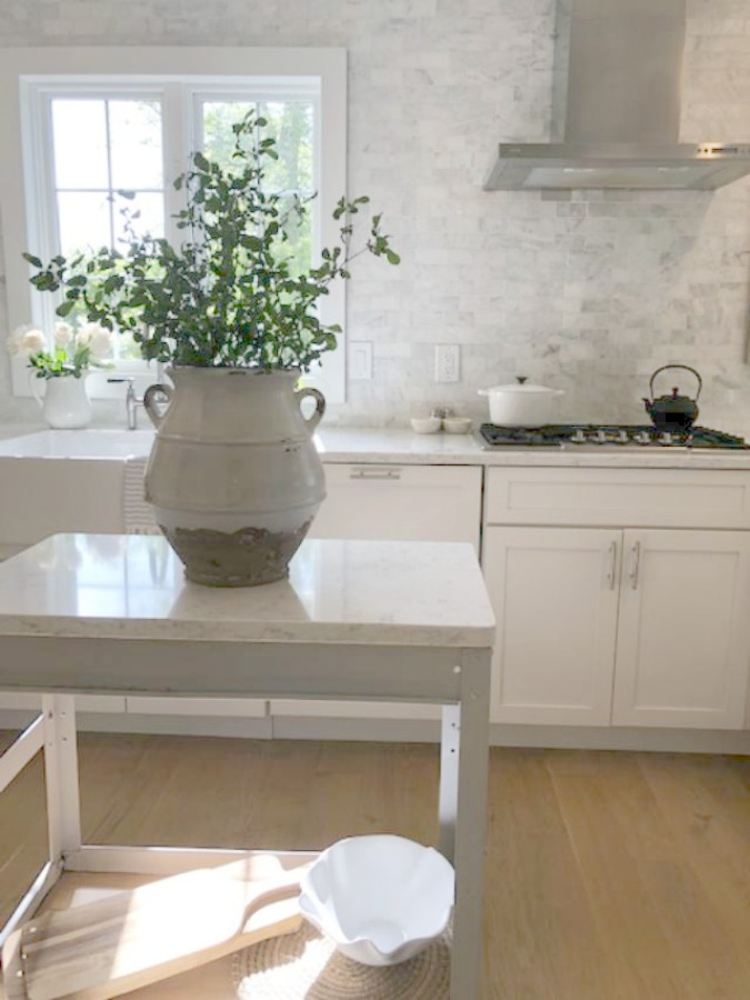 Serene tranquil white kitchen with farm sink, marble subway tile, Viatera Minuet quartz counters, white Shaker cabinets, and white oak flooring. Come explore How to Decorate a Room Without Breaking the Bank: Low Cost Design Reminders.