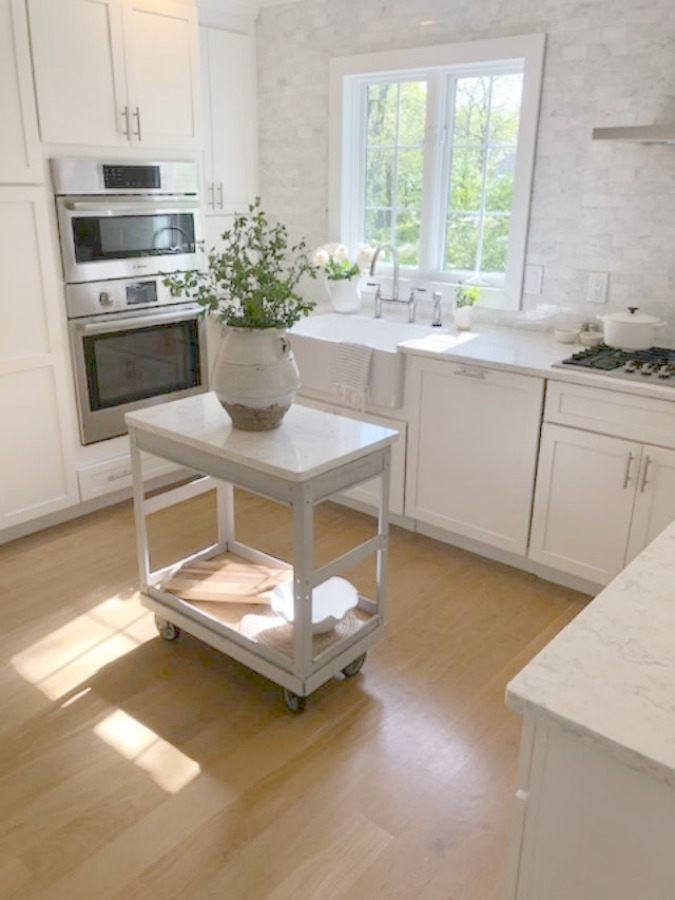 Serene tranquil white kitchen with farm sink, marble subway tile, Viatera Minuet quartz counters, white Shaker cabinets, and white oak flooring. Come explore Serene Decor Slow Living as well as Small Thoughtful Changes at Home.